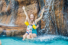 Mother and son relaxing under a waterfall in aquapark royalty free stock photo