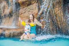 Mother and son relaxing under a waterfall in aquapark stock photos