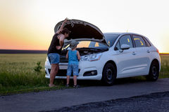 Mother and Son Repairing Something on their Car Stock Photo