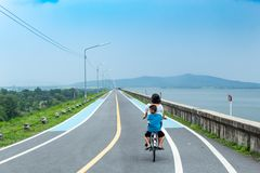 Mother and son ride this road on the reservoir. royalty free stock photo