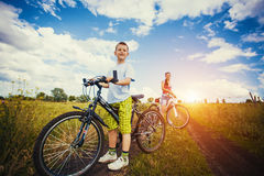 Mother and son riding bicycle in the field Stock Photo