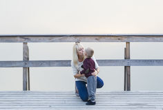 Mother with the son are on the river jetty. Fog. Sunset. Royalty Free Stock Photography