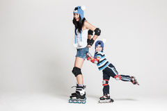Mother and son in roller skates. Good looking family, mother and son, posing in studio wearing inline rollerskates and matching funny hats, isolated on white Royalty Free Stock Photo