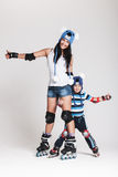 Mother and son in roller skates. Good looking family, mother and son, posing in studio wearing inline rollerskates and matching funny hats, isolated on white Royalty Free Stock Photography