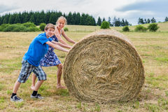 Mother and son rolling hay bale in countryside Royalty Free Stock Images