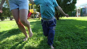 Mother and son running barefoot on the grass stock video