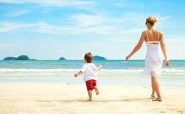 Mother and son running on beach Stock Photo