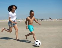 Mother and son running on beach with ball Stock Photos
