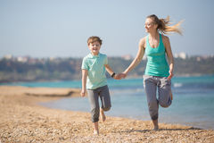 Mother with son running on the beach Stock Image