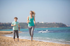 Mother with son running on the beach Royalty Free Stock Photos