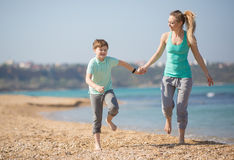Mother with son running on the beach Stock Photo