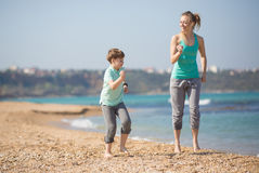 Mother with son running on the beach Stock Images