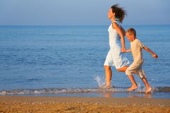 Mother with son running on edge of sea Royalty Free Stock Image