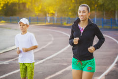 Mother and son are running or jogging for sport outdoors stock photo