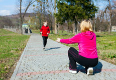 Mother with the son running on park. Mother with happy son running on park royalty free stock image