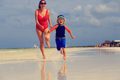 Mother and son running on tropical beach Royalty Free Stock Photos