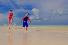 Mother and son running on tropical beach Royalty Free Stock Photography