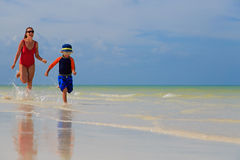 Mother and son running in water on the beach Stock Image