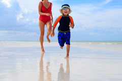 Mother and son running in water on the beach Stock Photo