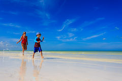 Mother and son running in water on the beach Stock Photography