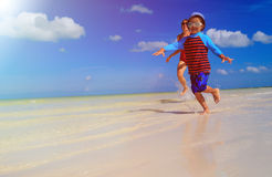 Mother and son running in water on the beach Royalty Free Stock Photos