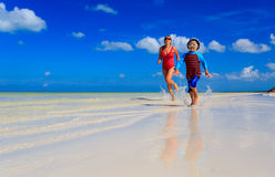 Mother and son running in water on the beach Royalty Free Stock Images