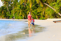 Mother and son running in water on beach Royalty Free Stock Images