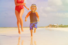 Mother and son running in water on beach Royalty Free Stock Photo