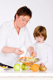 Mother and son and the salad. Mother and son making a healthy fruit salad Stock Images