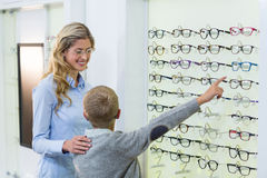 Mother and son selecting spectacles from display Royalty Free Stock Images