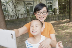 Mother and son self shot. Chinese mother and son self shot ahead house with smartphone Royalty Free Stock Photos