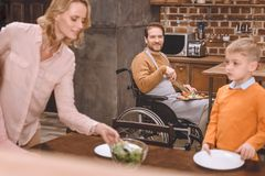 Mother with son serving table for dinner while father in wheelchair cutting vegetables. At home Royalty Free Stock Images