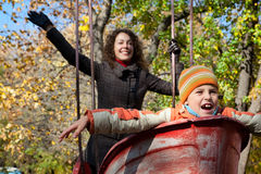 Mother with son shake on swing in autumnal park Stock Photos