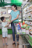 Mother and son shopping for groceries in supermarket, buying watermelon Stock Images