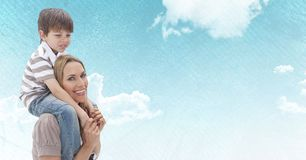 Mother with son on shoulders against sky Stock Photo