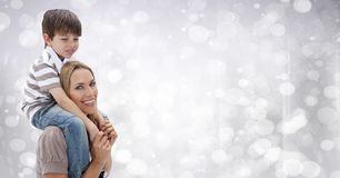 Mother with son on shoulders against white bokeh Royalty Free Stock Images