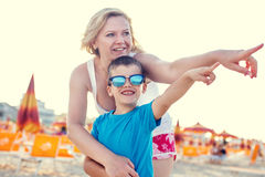 Mother with son showing away on beach Stock Image