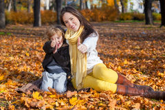 Mother and son showing thumbs up in park. Happy mother and son sitting on autumn leaves and showing thumbs up stock photography