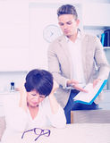 Mother and son sign documents. Senior mother was has turned away from the son who suggests her to sign documents royalty free stock photography