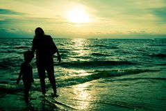 Mother and son silhouette sunset on beach royalty free stock photos