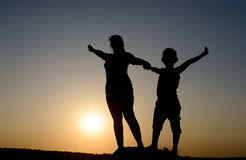 Mother and son silhouetted by the setting sun Royalty Free Stock Photo