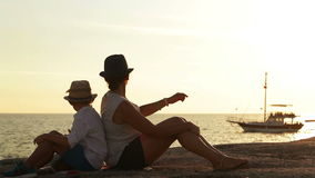 Mother and son sit on the beach at sunset watching a ship go by stock video footage