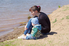 Mother and son sit on the riverside Royalty Free Stock Photography