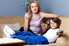 Mother and son sit on the sofa and watch tv. Young mother with her son relax on the sofa and watch tv, he holds tv remote Royalty Free Stock Photos