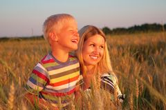 Mother and son  sit on wheaten field Royalty Free Stock Images