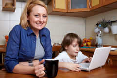 Mother and son sits in kitchen and use laptop. Mother and her son sits at kitchen table and play with small laptop Stock Image