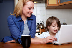 Mother and son sits in kitchen and use laptop. Mother and her son sits at kitchen table and play with small laptop Stock Photography