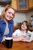 Mother and son sits in kitchen and use laptop Stock Image