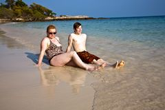 Mother and son sitting at a beautiful sandy beach Stock Photos