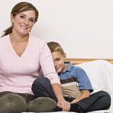 Mother and Son Sitting on Bed Stock Photo